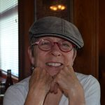 Headshot of Carol Whitman wearing a cap